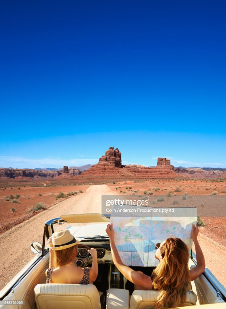 Women reading map in convertible on remote road : Stock Photo