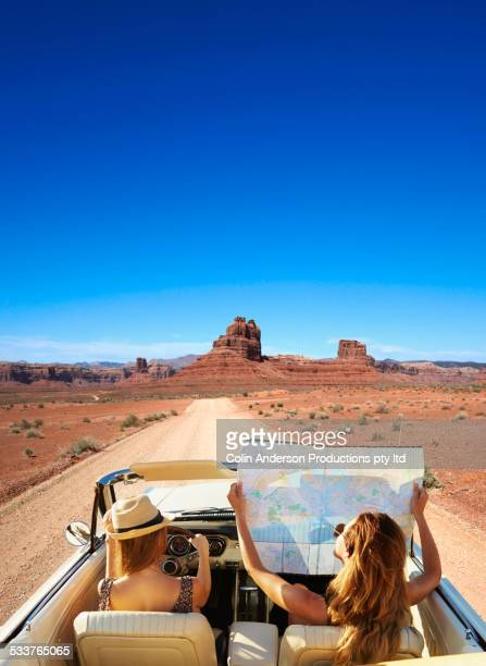 women reading map in convertible on remote road - road trip stock photos and pictures