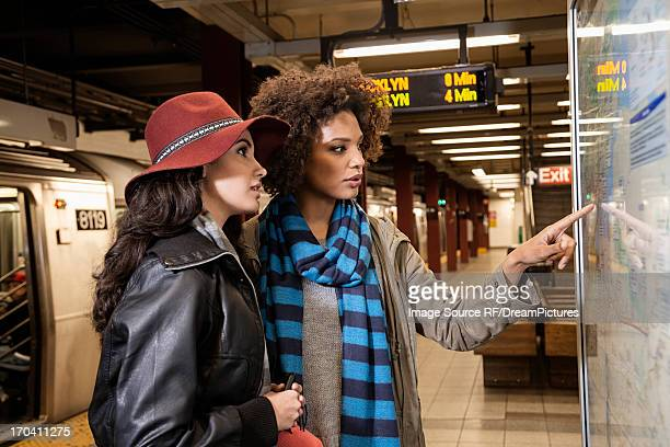 Women reading map in subway station