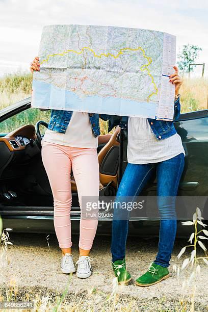 Women reading map on road trip