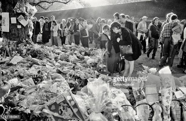 Women reading the messages on the hundreds of bouquets of flowers lining the length of the Mall between Buckingham Palace and Whitehall during the...