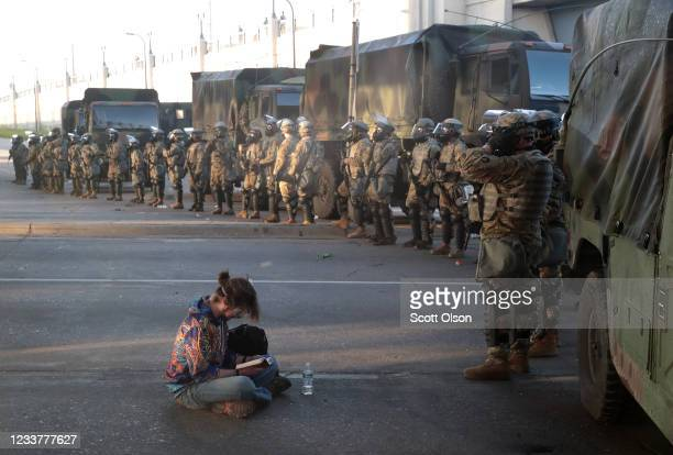A women reads a bible in front of a line of National Guardsmen as the 8pm curfew approaches during protests sparked by the death of George Floyd...