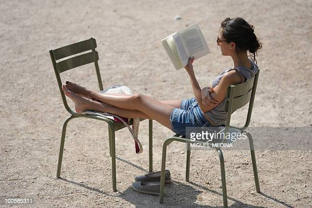 A women reads a book under the sun in the Luxembourg gardens in Paris on July 1 2010 during a heatwave as temperatures soared all over the country...