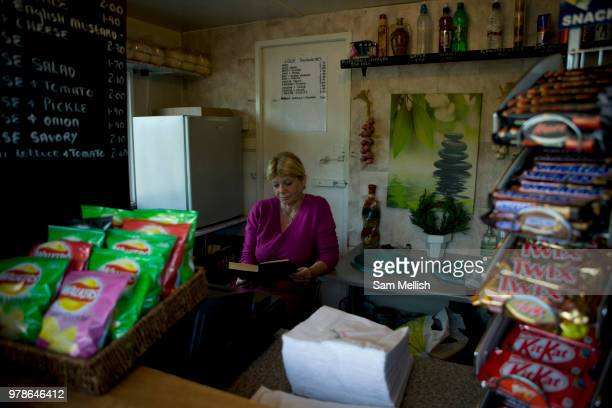 A women reads her book in her neatly arranged burger van along the A1 on the 10th May in Newcastle in the United Kingdom