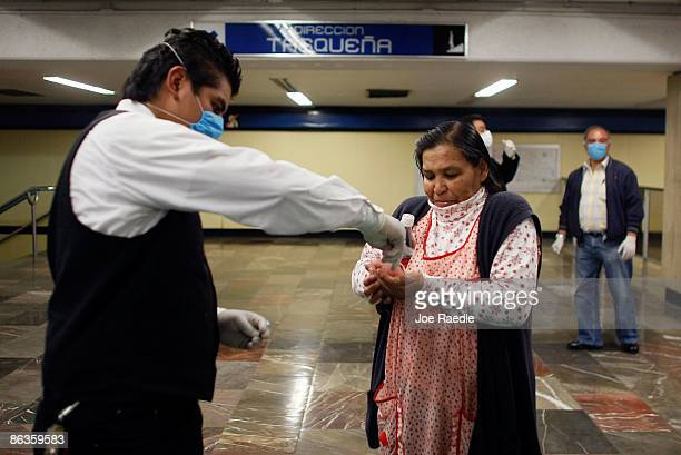 A women receives hand cleaner to help prevent catching the swine flu as she navigates the subway system on May 3 2009 in Mexico City Mexico The...