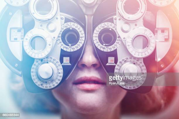women receiving eye exam - optometry stock pictures, royalty-free photos & images