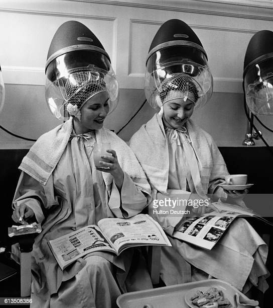 Women relax as they sit under hair dryers at the Valentino & Rita of Knightsbridge beauty salon in London, England.