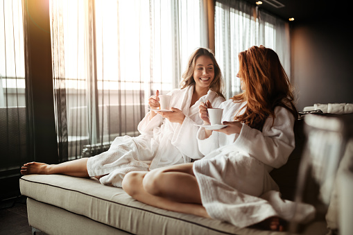 Women relaxing and drinking tea in robes during wellness weekend 665371624