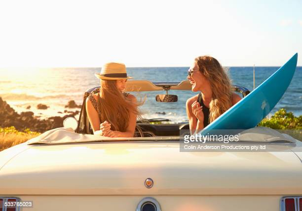 Women relaxing in convertible on beach