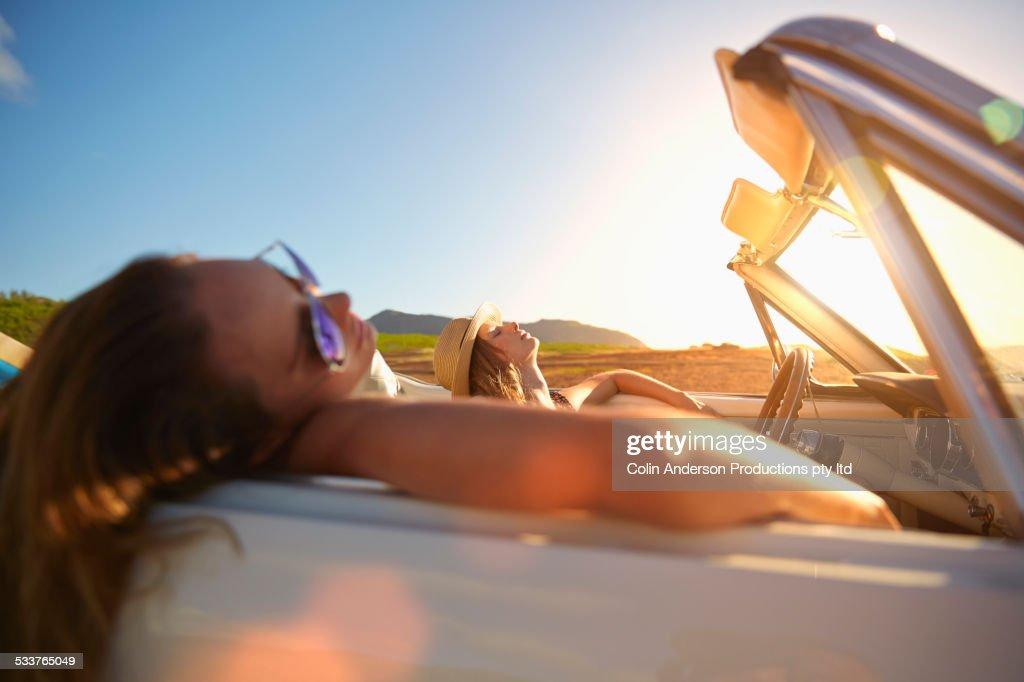 Women relaxing in convertible on beach : Foto stock