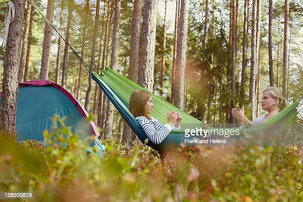 Women relaxing in hammock at campsite