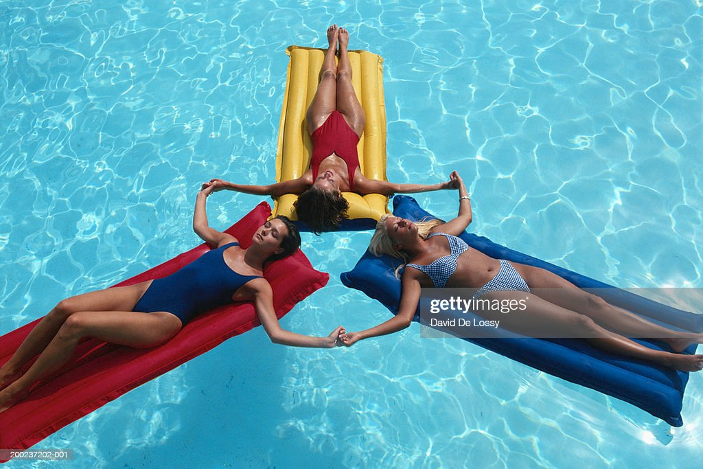 Women relaxing on airbeds, holding hands, elevated view : Stock Photo