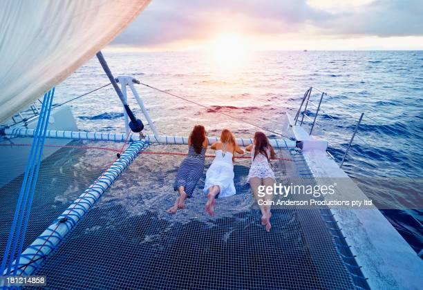 women relaxing on boat in ocean - catamaran fotografías e imágenes de stock
