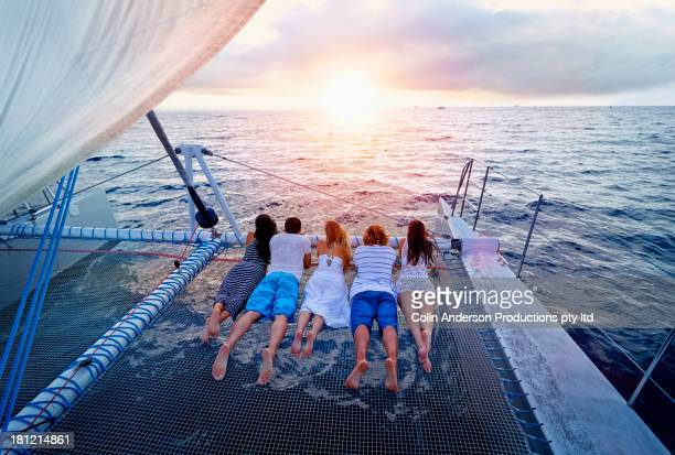 women relaxing on boat in ocean - catamaran stock photos and pictures