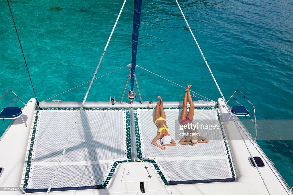 Women relaxing on catamaran in the Caribbean : Stock Photo