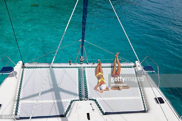 women relaxing on catamaran in the caribbean - catamaran stock photos and pictures
