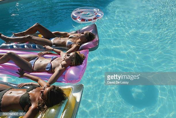 Women relaxing on pool raft in swimming pool, elevated view