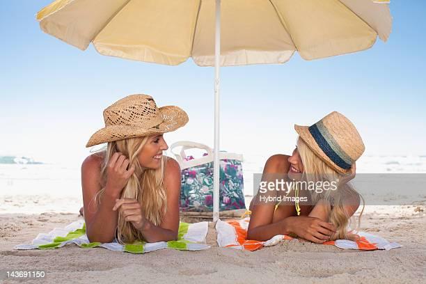 Women relaxing under umbrella on beach