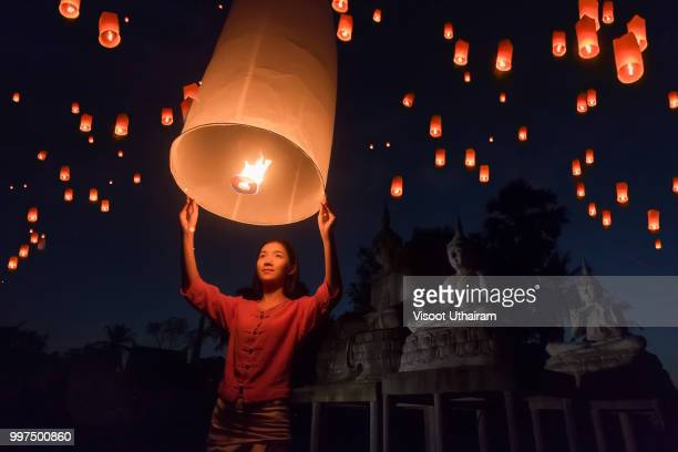 women release khom loi, the sky lanterns during yi peng or loi krathong festival - releasing stock pictures, royalty-free photos & images