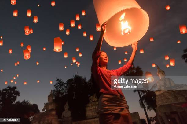 women release khom loi, the sky lanterns during yi peng or loi krathong festival - releasing stock photos and pictures