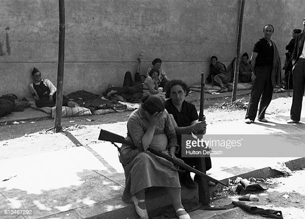 Women republicans look despairing as they sit at the side of the road with rifles during the Spanish Civil War