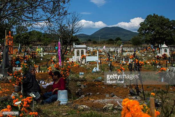 Women rest in a cemetery at the outskirt of Patzcuaro which people remember those relatives and friends that have passed away on November 01 2014 in...