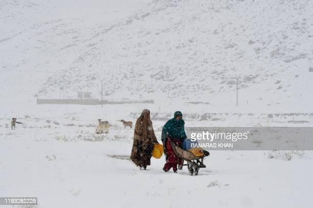 Women return after getting drinking water during a snowfall in Quetta on January 12 2020