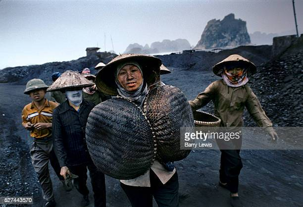 Women returning with their empty baskets to the mine having just loaded coal anthracite onto barges for export The mine in Cam Pha northern Vietnam...