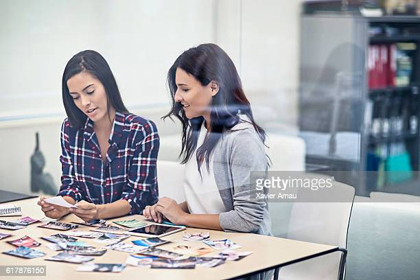 women reviewing picture in office meeting - printout stock pictures, royalty-free photos & images
