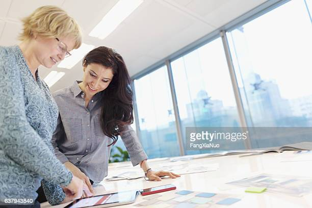 women reviewing plans on tablet computer in studio - intellectual property stock pictures, royalty-free photos & images