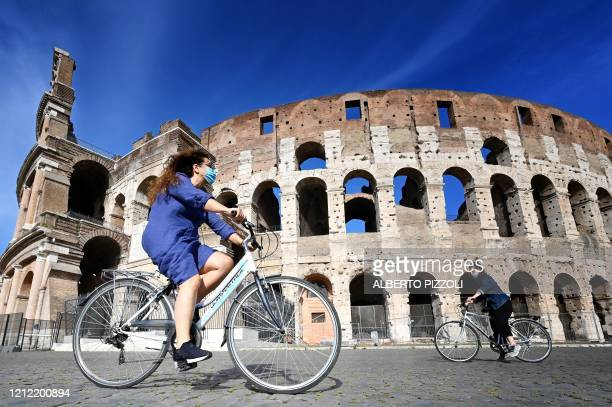 TOPSHOT Women ride a bicycle past the Colosseum monument in Rome on May 8 during the country's lockdown aimed at curbing the spread of the COVID19...