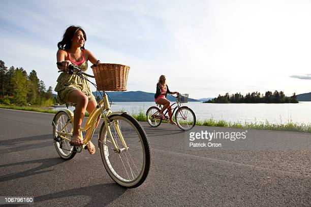 women ride beach cruisers next to the lake in idaho. - teenagers only stock pictures, royalty-free photos & images