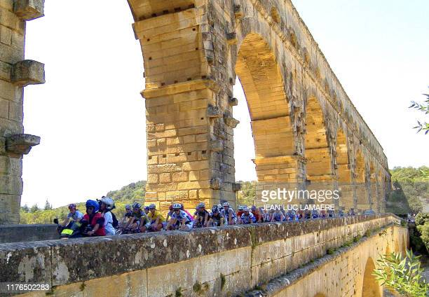 """Women ride on the Gard bridge during the fourth stage of the French """"Grande Boucle"""" cycling race, 29 June 2006 near Remoulins, southern France. AFP..."""