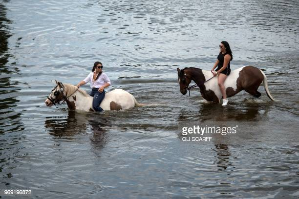 Women ride their horses into the River Eden on the opening day of the annual Appleby Horse Fair in the town of ApplebyinWestmorland northwest England...