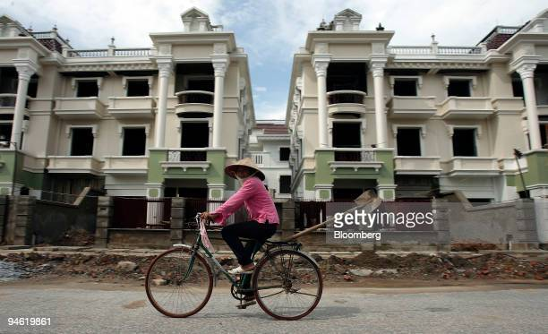 A women rides her bike past residential apartments under construction in a suburb of Hanoi Vietnam on Sunday August 20 2006