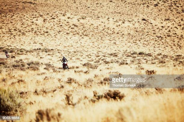 Women riding dirt bikes in desert on summer afternoon