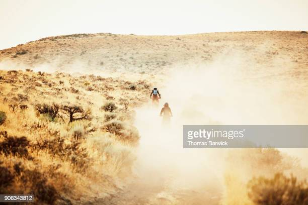 Women riding dirt bikes on dusty desert road on summer evening