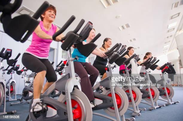 Women riding exercise bikes in health club