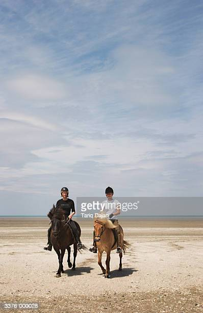Women Riding Ponies on Beach