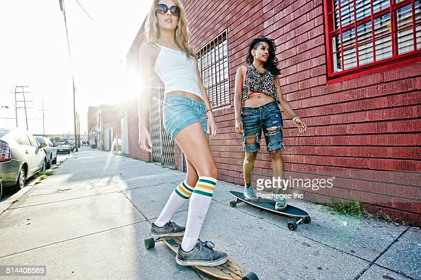 Women riding skateboards on city street