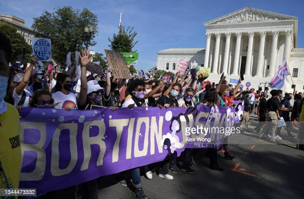 Women rights activists participate in the annual Women's March as they pass by the U.S. Supreme Court October 2, 2021 in Washington, DC. The annual...
