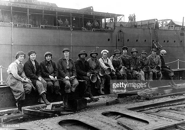 Women rivet heaters and passers who work in a Navy shipyard on Washington's Puget Sound sit on the edge of a wharf May 1919   Location Washington USA