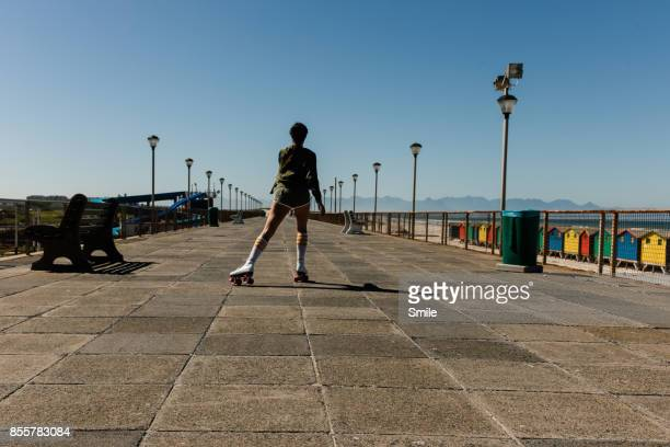 Women roller skating on the boardwalk, from behind