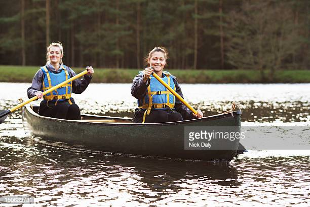 women rowing canoe on still lake - canoe stock pictures, royalty-free photos & images