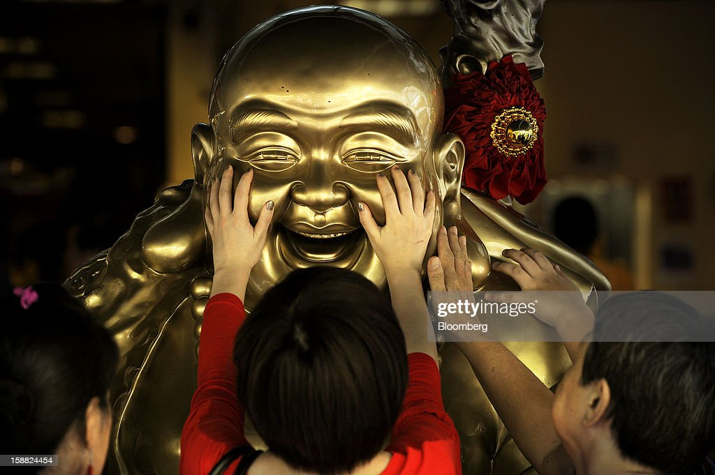 Women rub the face of a laughing buddha statue near a Chinese temple in Singapore, on Sunday, Dec. 30, 2012. Singapore may grapple with elevated inflationary pressures for a third year in 2013, reducing scope for the central bank to provide stimulus to an economy that probably entered a technical recession this quarter. Photographer: Munshi Ahmed/Bloomberg via Getty Images