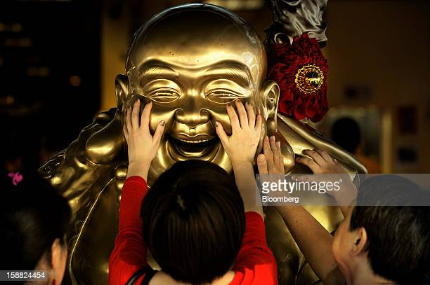 Women rub the face of a laughing buddha statue near a Chinese temple in Singapore on Sunday Dec 30 2012 Singapore may grapple with elevated...