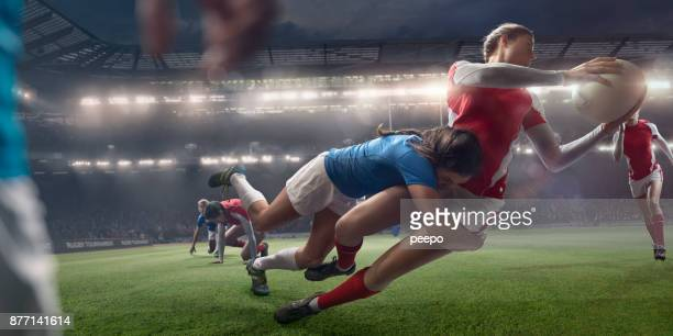 women rugby players in mid tackle during stadium rugby match - tackling stock pictures, royalty-free photos & images