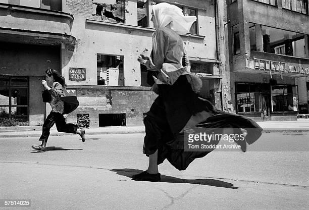 Women run across 'Sniper Alley' during heavy shooting in Sarajevo in 1993.