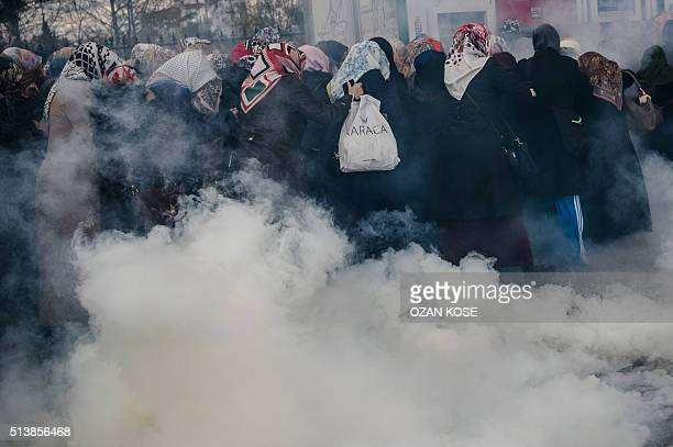 Women run as Turkish antiriot police officers use tear gas to disperse supporters in front of the headquarters of the Turkish daily newspaper Zaman...