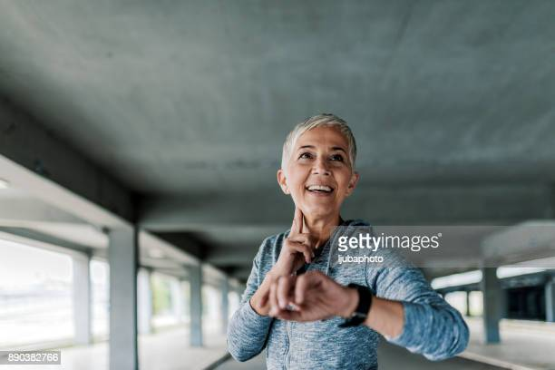 women runner taking pulse - heart health stock pictures, royalty-free photos & images